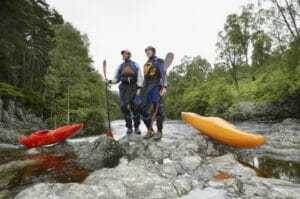 Kayakers on standing on river rocks