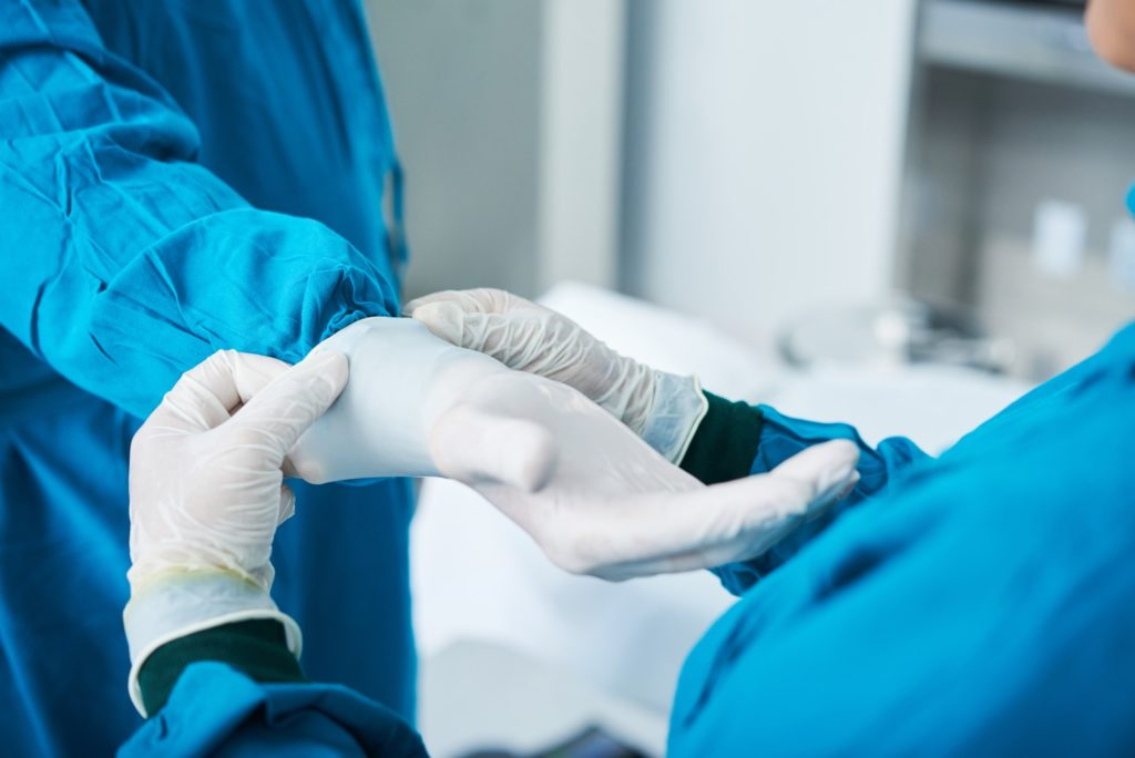 Crop assistant putting on glove on surgeon hand